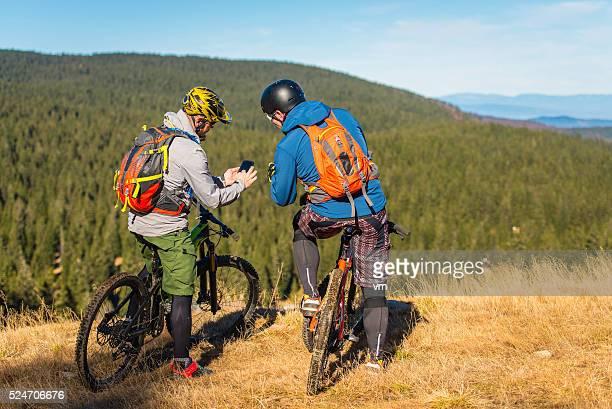 cruz país los ciclistas observando un teléfono inteligente - cross country cycling fotografías e imágenes de stock