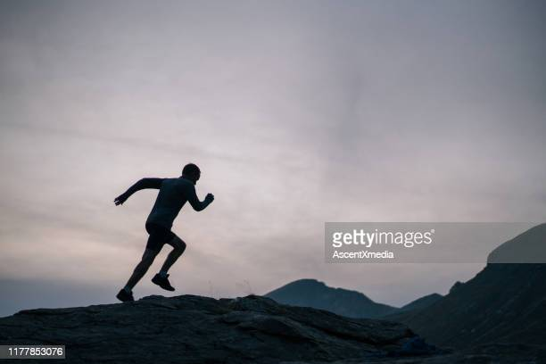 cross country runner bounds up mountain - striding stock pictures, royalty-free photos & images