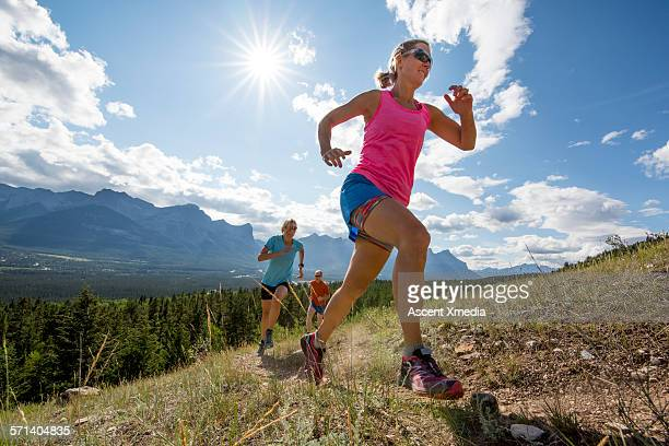 cross country runners ascend mountain trail - blue shorts stock pictures, royalty-free photos & images