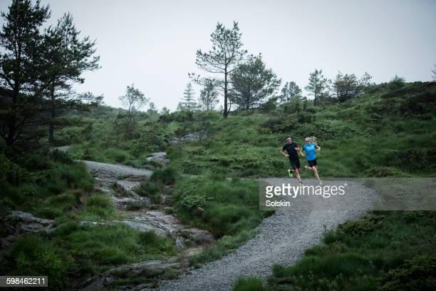 cross country running couple on dirt road - cross country cycling fotografías e imágenes de stock