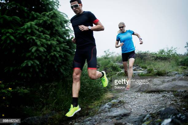 Cross country running couple on rocky road