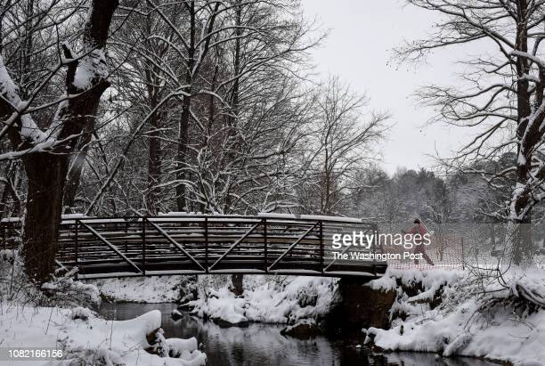 A cross country skier approaches a bridge over Sligo Creek during the first significant snow of the new year on January 2019 in Silver Spring MD