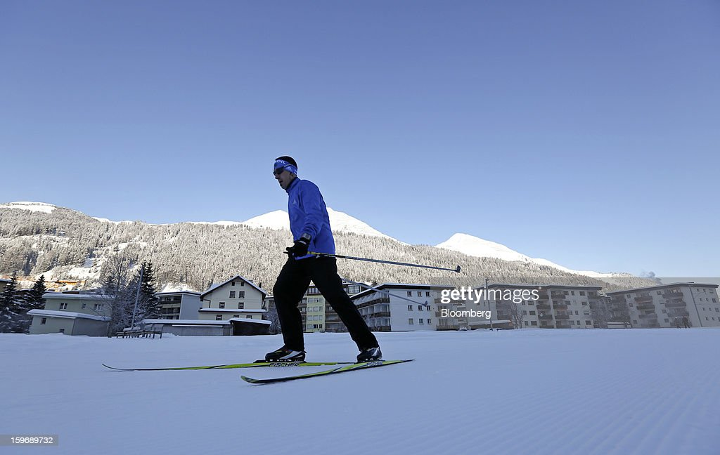A cross country skier passes residential homes as he makes his way along a track in Davos, Switzerland, on Friday, Jan. 18, 2013. Next week the business elite gather in the Swiss Alps for the 43rd annual meeting of the World Economic Forum in Davos, the five day event runs from Jan. 23-27. Photographer: Chris Ratcliffe/Bloomberg via Getty Images