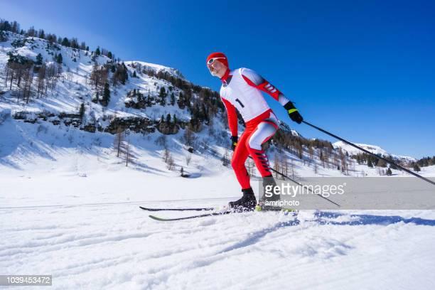 冬の晴れた日に斜面の上でスケート クロスカントリー スキーヤー