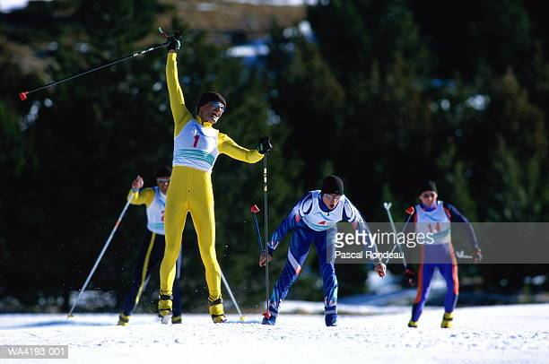 Cross country skier with arm raised in air, other skiers behind him