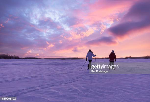 cross country skiing into the sunset on a lake in minnesota - schemering stockfoto's en -beelden