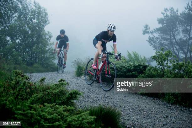 cross cycling man and woman on dirt road - road cycling stock pictures, royalty-free photos & images