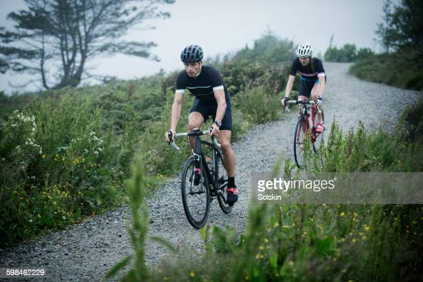 cross cycling man and woman on dirt road - gravel stock pictures, royalty-free photos & images