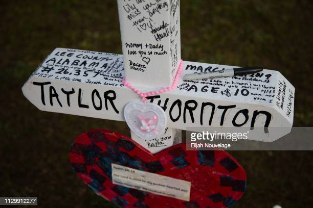 A cross decorated with messages for Taylor Thornton one of the 23 victims of an EF4 tornado is seen on the grounds of Providence Baptist Church on...