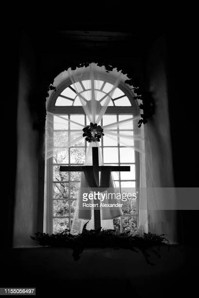 A cross draped in white is displayed after Easter in a window of the San Francisco de Asis Mission Church in Rancho de Taos New Mexico The historic...