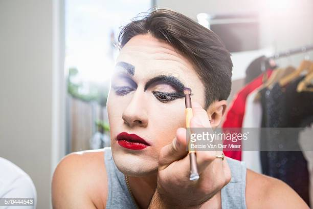 cross dresser applying eyeshadow. - transvestite stock photos and pictures
