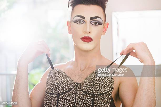 cross dresser holding dress in front of mirror - transvestite stock photos and pictures