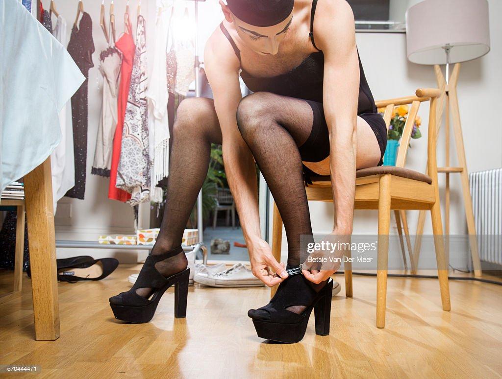 Cross dresser puts on high heel shoes. : Stock Photo
