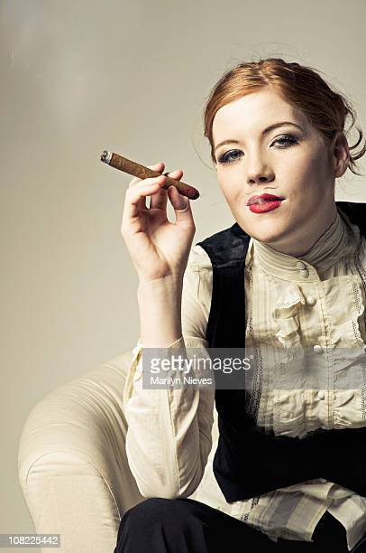 cross dresser relaxing with a cigar - beautiful women smoking cigars stock photos and pictures