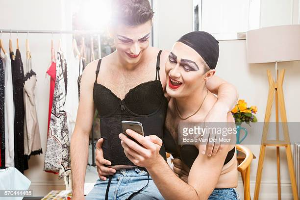 Cross dressing couple laughing at photos on phone.