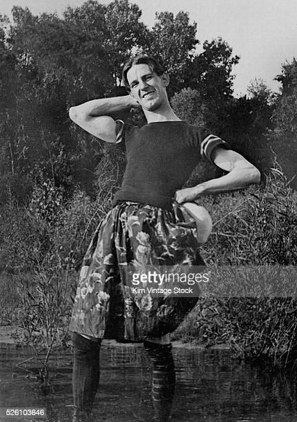A cross dressing man poses in his skirt while wading in the water ca 1910