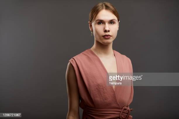 un retrato de estudio de cross vistiendo a un hombre en un fondo llano. - gender fluid fotografías e imágenes de stock