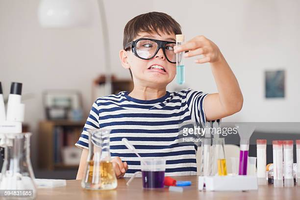 Cross eyed boy looking at test tube during science experiment in house