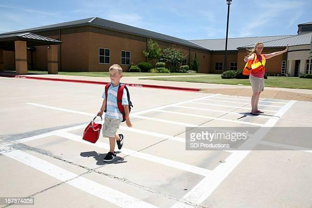 Cross Guard Helping Boy Walk Across The Street At School