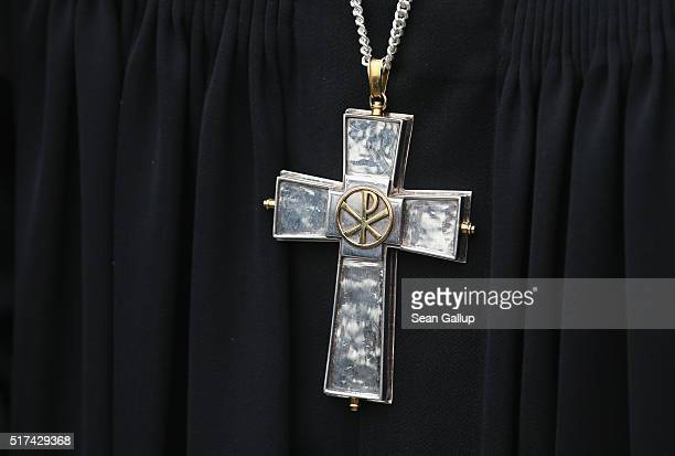 A cross hangs from the neck of a Protestant pastor during a Good Friday procession on March 25 2016 in Berlin Germany Christians across the globe...