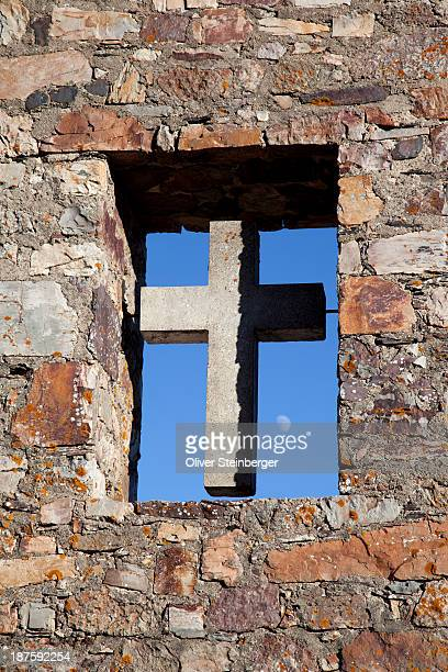 A cross in an open window of the stone wall of a church
