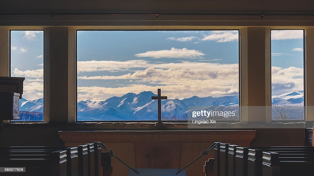 A cross inside Church with Mountain background : Stock Photo