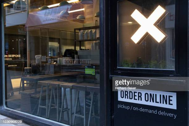 Cross is illuminated outside a coffee bar that, when open, serves online orders from its hatch, during the third lockdown of the Coronavirus...