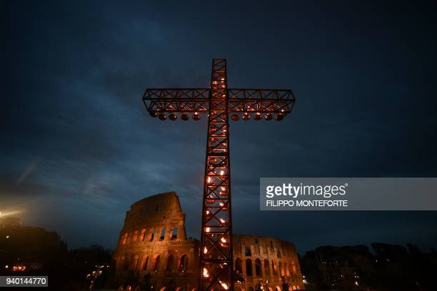 A cross is lighted before the arrival of Pope Francis for the Via Crucis torchlight procession at the ancient Colosseum on Good Friday on March 30...