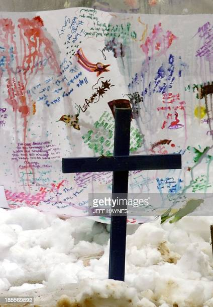A cross is planted in front of a banner at a memorial in Robert F Clement Park next to Columbine High School 23 April 1999 in Littleton CO where...