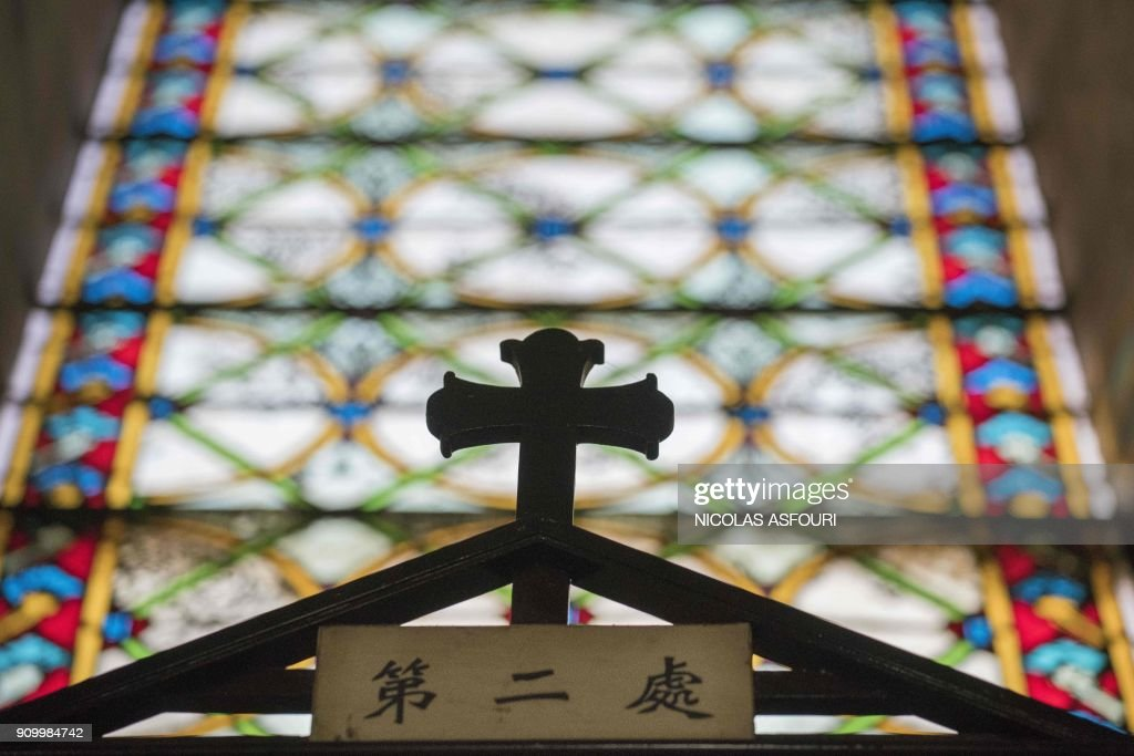 A cross is seen inside St. Joseph's church, also known as Wangfujing church in Beijing on January 25, 2018. / AFP PHOTO / Nicolas ASFOURI