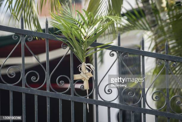 A cross of palm leaves hangs from a fence during Palm Sunday in Caracas Venezuela on Sunday April 5 2020 Amid the coronavirus as the world's major...
