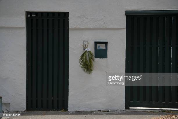 A cross of palm leaves hangs from a wall during Palm Sunday in Caracas Venezuela on Sunday April 5 2020 Amid the coronavirus as the world's major...