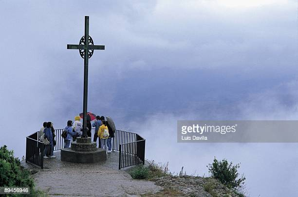 Cross of the viewpoint in Montserrat monastery Tourist in the Cross of the viewpoint in the Montserrat monastery 11th century