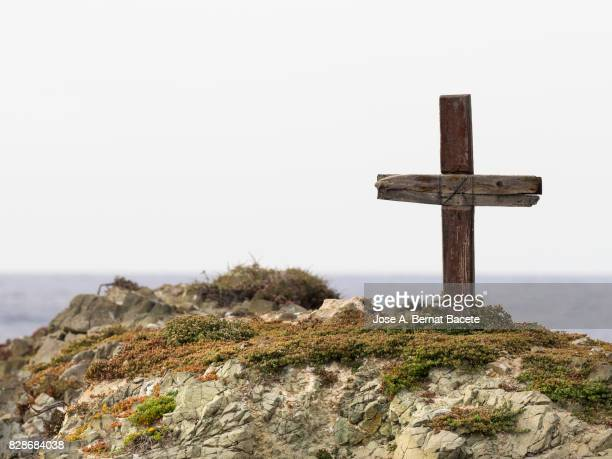Cross of wood on the top of a mountain in an island deserted.  Tabarca Island in Alicante, Valencian Community, Spain.