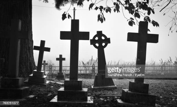 cross on cemetery against sky - gravestone stock pictures, royalty-free photos & images