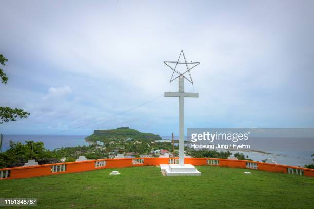 cross on field against sea - saipan stock pictures, royalty-free photos & images