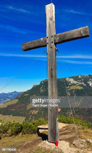 Cross On Landscape Against Blue Sky