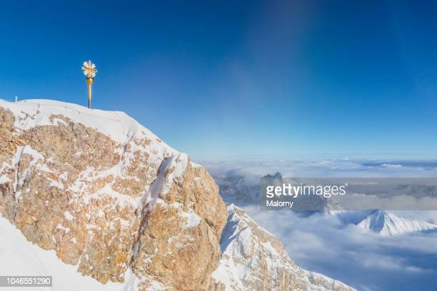 cross on the summit of mount zugspitze. wetterstein mountains, bavaria, germany. - garmisch partenkirchen stock pictures, royalty-free photos & images