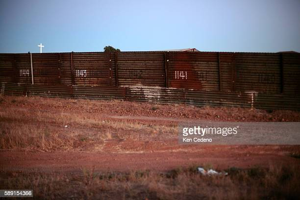 A cross pokes it's way into view from Tijuana Mexico at the USMexico border on August 27 2006