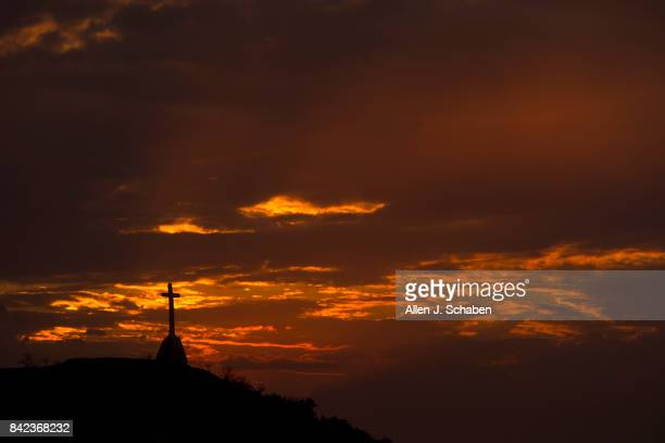 A cross remains standing amid the scorched hillside that destroyed three homes and a shed and is silhouetted at sunset in the the La Tuna Canyon fire...
