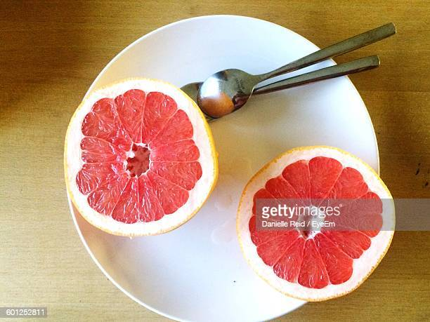 cross section of grapefruit on plate - danielle reid stock pictures, royalty-free photos & images