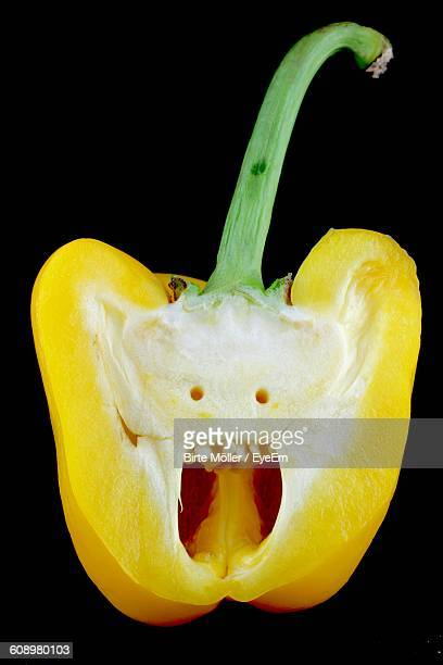 cross section of yellow bell pepper against black background - anthropomorphic face stock pictures, royalty-free photos & images