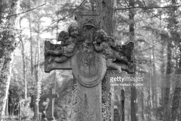 Cross Shaped Tombstone With Angel Carvings In Cemetery