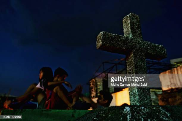 A cross sign is seen at a cemetery during the commemoration of All Saints' Day in Manila on November 1 2018 in Manila Philippines Filipinos flock to...