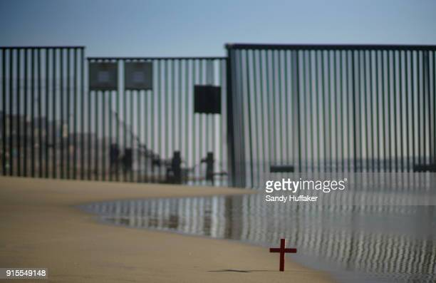 A cross sits in the sand in front of the USMexico border planted by activists in support of passage of the Dream Act February 7 2018 in San Ysidro...