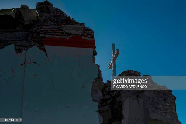 A cross stands on top of the Inmaculada Concepcion church built in 1841 seen partially collapsed after an earthquake hit the island in Guayanilla...