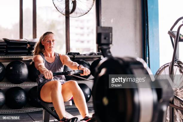 cross training and rowing on the machine in gym - rowing stock pictures, royalty-free photos & images