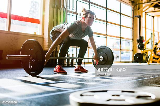 cross training woman performing deadlift - snatch weightlifting stock photos and pictures