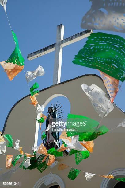 cross, virgin mary and prayer flags atop a church - timothy hearsum fotografías e imágenes de stock