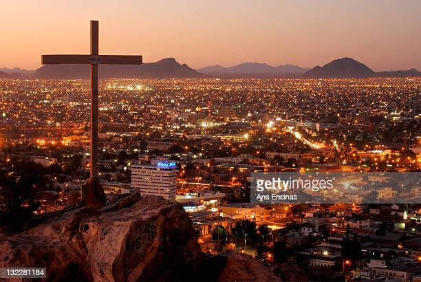 cross with cityscape at night - sonora mexico stock photos and pictures